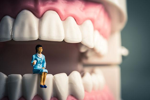 Woman sitting on giant teeth